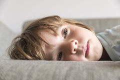 Little girl watching TV. On the couch stretched Stock Photo