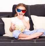 Little girl watching TV. Little girl eating popcorn and watching 3d TV Stock Photography