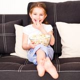 Little girl watching TV. Girl eating popcorn in front of TV Royalty Free Stock Images