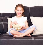 Little girl watching TV. Little girl eating popcorn in front of TV Royalty Free Stock Photography