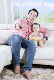 Little girl watching TV with her father. Little girl eating popcorn and watching TV with her father while sitting on the couch Stock Photography