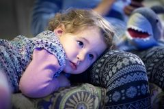 Little girl is watching TV at home Stock Photo