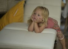 Little girl watching TV lying on the couch. The child is absorbed in watching TV,sitting comfortably on the couch Royalty Free Stock Photography