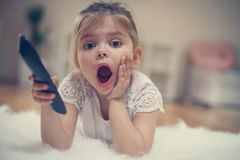 Little girl watching TV. Portrait. Close up image. Looking at camera Stock Images