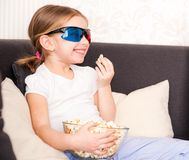 Little girl watching TV. Pretty little girl eating popcorn and watching 3d TV Royalty Free Stock Photo