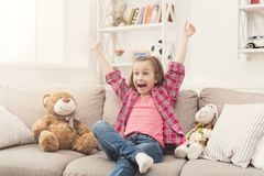 Little girl watching tv while sitting on sofa. Happy little casual girl watching tv at home. Excited female kid sitting on sofa with her toy friends teddy bear Royalty Free Stock Photography