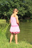 Little girl watching water in pond. Little girl in pink dress standing on green grass by a pond and watching water Stock Photography