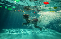 The little girl in the water park swimming underwater and smiling Royalty Free Stock Photo