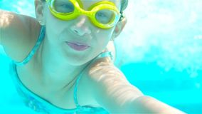 The little girl in the swimming pool underwater and smiling. The little girl in the water park swimming underwater and smiling stock footage