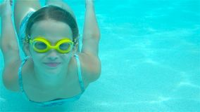 The little girl in the swimming pool underwater and smiling. The little girl in the water park swimming underwater and smiling stock video