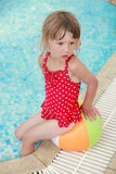 Little girl in the water pool with a ball Stock Photography
