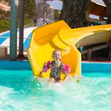 Little girl on water slide at aquapark during Stock Photography
