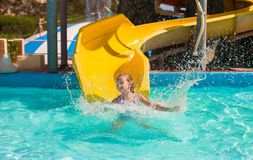 Little girl on water slide at aquapark during Stock Photo