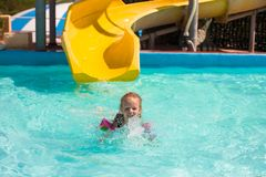 Little girl on water slide at aquapark during Stock Images