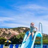 Little girl on water slide at aquapark during Stock Image