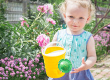 Little girl with a watering can for flowers. Stock Photo