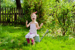 Little girl with a watering can in the garden. Girl with a watering can in the garden stock images