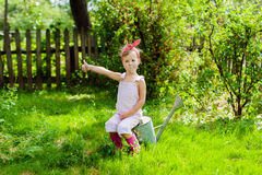 Little girl with a watering can in the garden. Girl with a watering can in the garden royalty free stock image