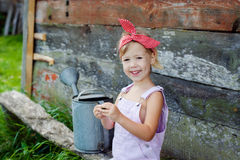 Little girl with a watering can in the garden royalty free stock images