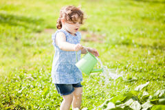 The little girl with the watering can in the garden. Horizontal photo of a toddler girl having fun watering vegetable garden bed stock photography