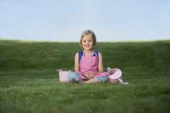 Little girl with watering can in the garden Stock Photos