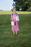 Little girl with watering can in the garden Stock Images