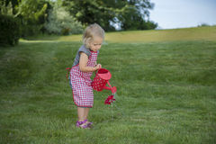 Little girl with watering can in the garden Royalty Free Stock Photo