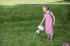 Little girl with watering can in the garden Royalty Free Stock Photos