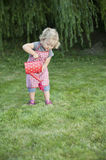 Little girl with watering can in the garden Royalty Free Stock Photography