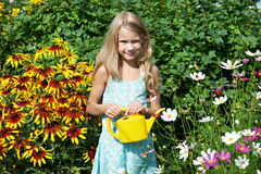 Little girl with watering can near flowers Royalty Free Stock Images