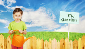 Little girl with a watering can next to fence of the garden Stock Photos