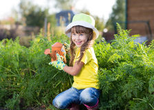 Little girl watering with can in the vegetables Royalty Free Stock Photo