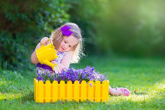 Little girl watering farden flowers Royalty Free Stock Image