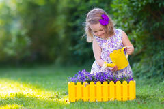 Little girl watering farden flowers stock photography