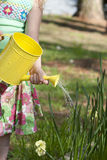 Little girl watering flowers Stock Images