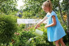 Little girl watering the flowers in the family garden at a summe Stock Photography
