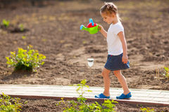 Little girl watering flowers in the garden Royalty Free Stock Images