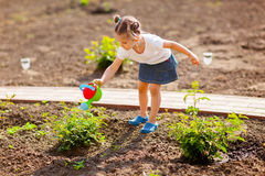 Little girl watering flowers in the garden Stock Photography