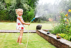 Little girl watering flowers in the garden Stock Photos