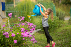 Little girl watering flowers near the house . Royalty Free Stock Images