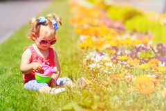 Little girl watering flowers in summer Stock Images