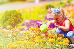 Little girl watering flowers in summer Royalty Free Stock Photography