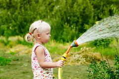 Little girl watering in the garden Royalty Free Stock Image