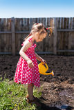 Little girl watering the garden Stock Images