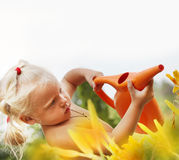 Little girl watering grass Stock Images