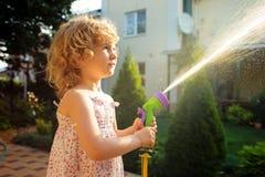 Little girl watering the grass in the garden Stock Photos