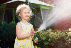Little girl watering the grass in the garden stock photography