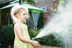 Little girl watering the grass in the garden Royalty Free Stock Photos