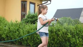 Little girl watering green grass in the garden. Cute little girl is holding the sprinkle and spraying the lawn on a stock video