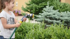 Little girl watering green grass in the garden. Cute little girl is holding the sprinkle and spraying the lawn on a stock video footage